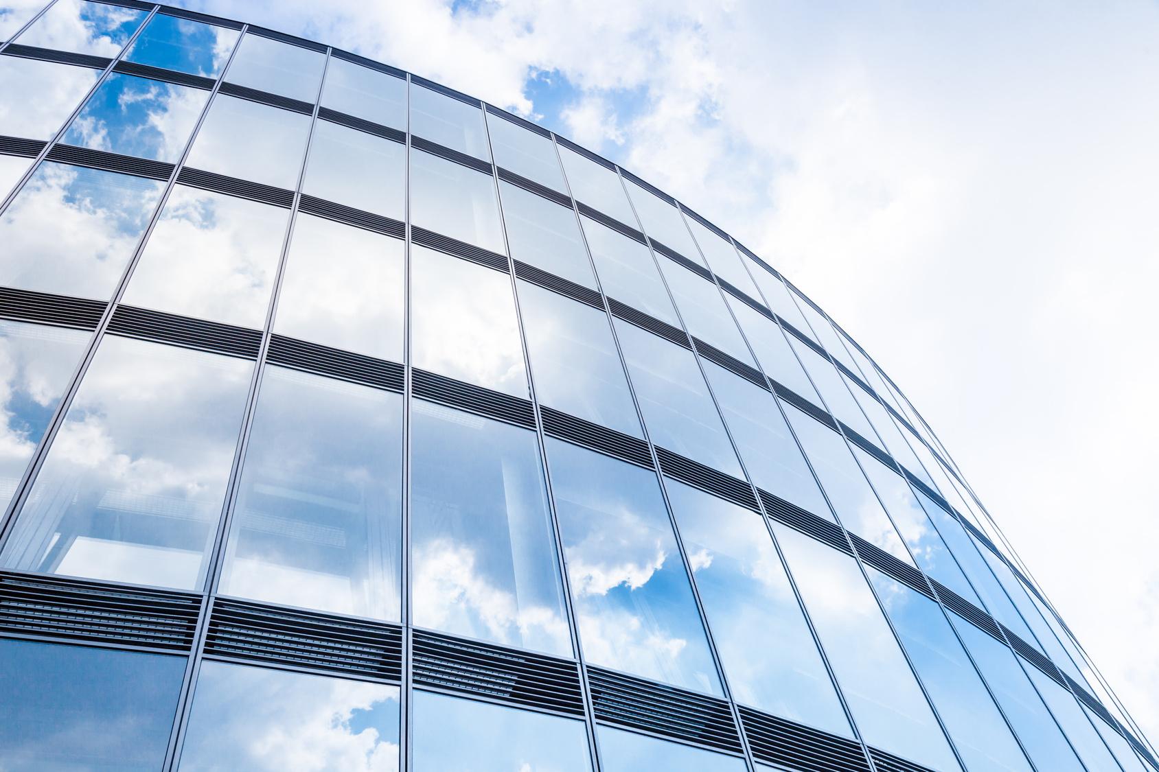 Imagen de un edificio con cristaleras azules y con el cielo azul de fonto